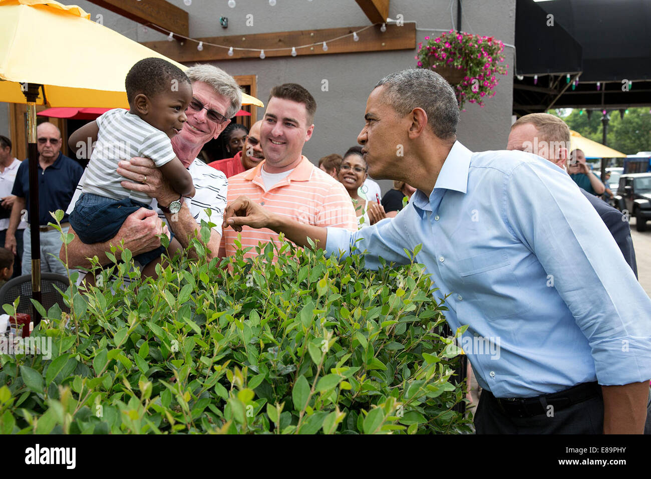 President Barack Obama jokes with a youngster while walking down Grand Avenue in St. Paul, Minn., June 26, 2014. - Stock Image