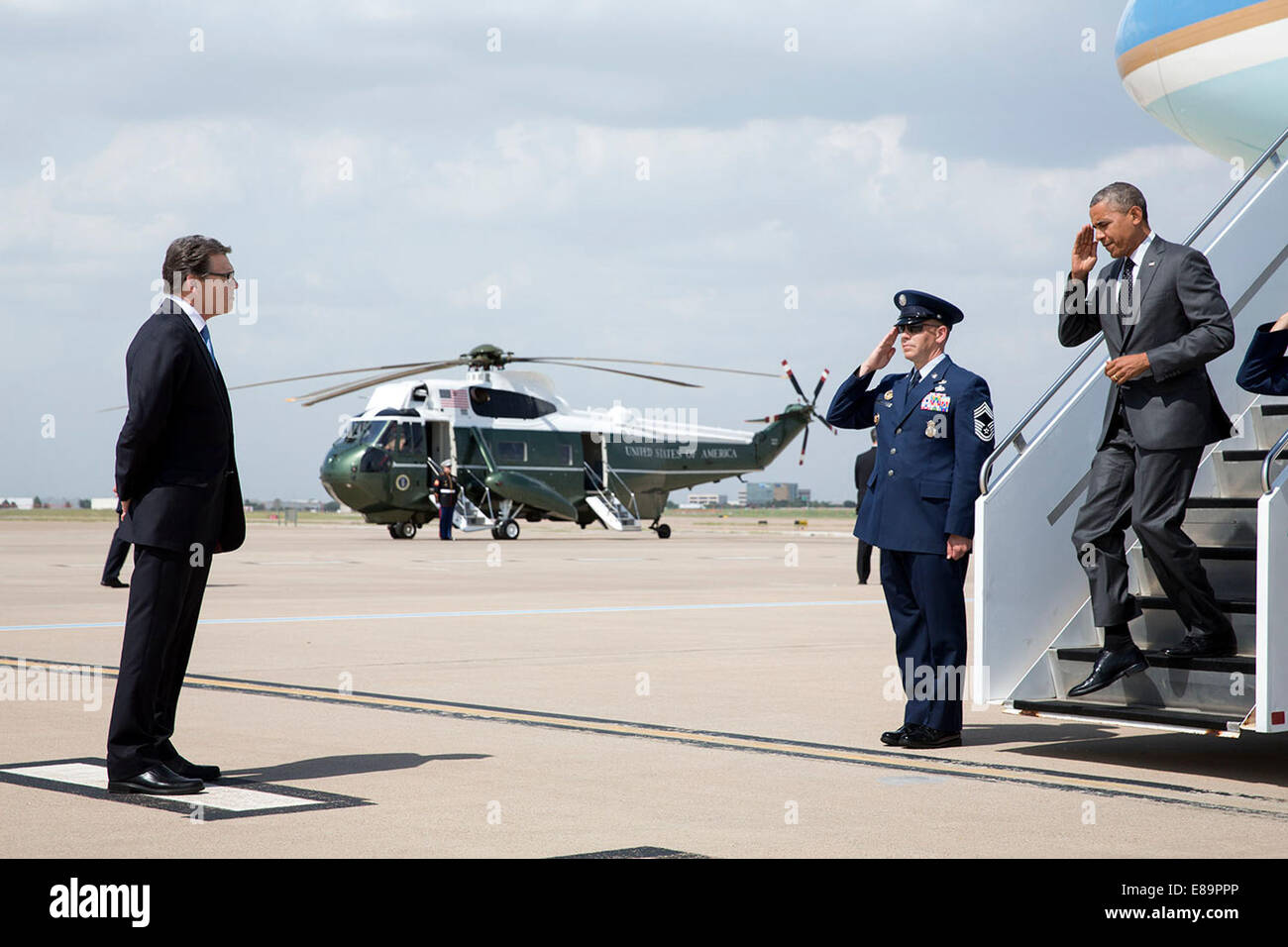 President Barack Obama salutes an Air Force member as he disembarks Air Force One to greet Gov. Rick Perry, R-Texas, - Stock Image