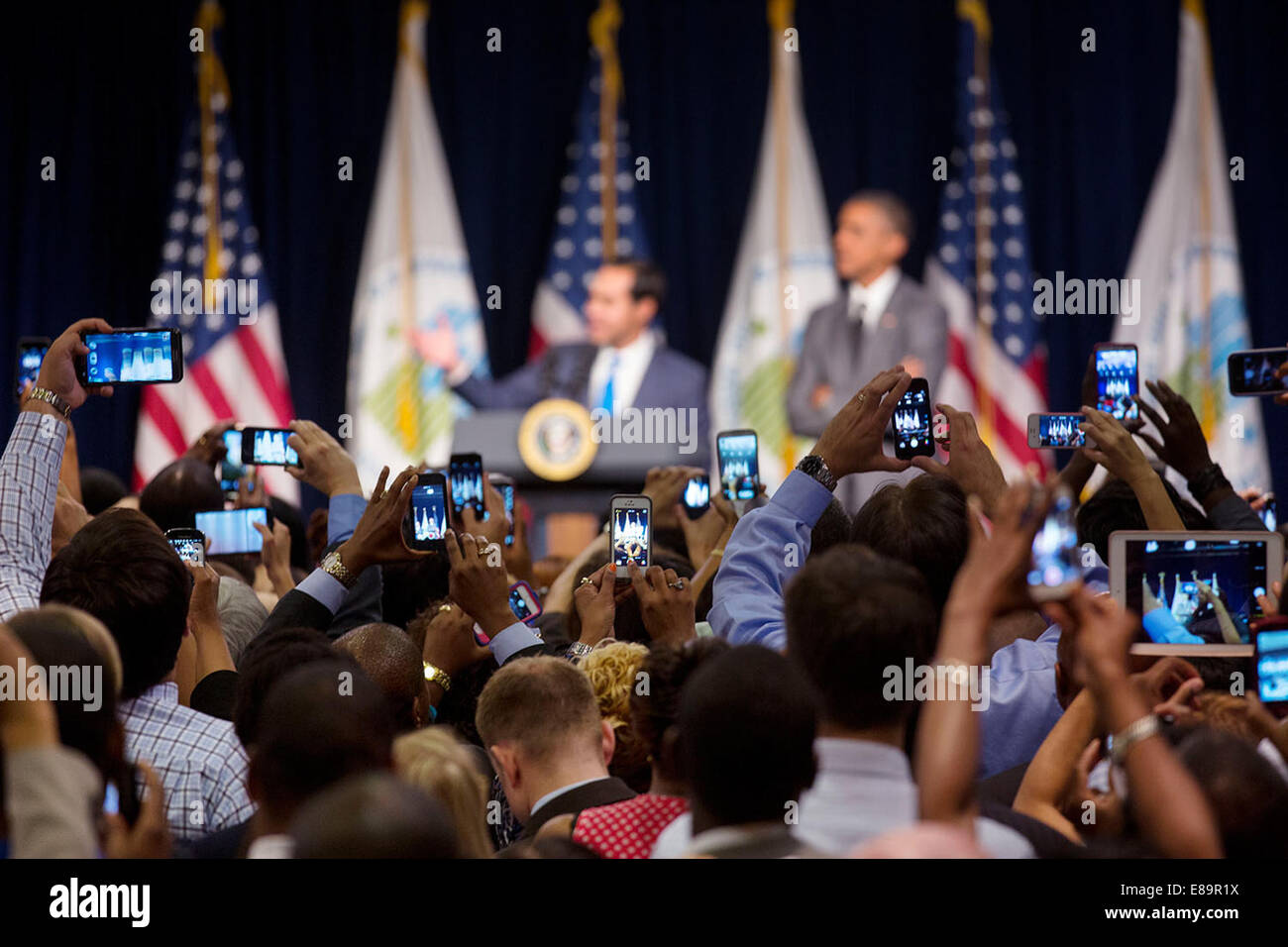 Audience members photograph HUD Secretary Juli‡n Castro introducing President Barack Obama at the Department of Stock Photo