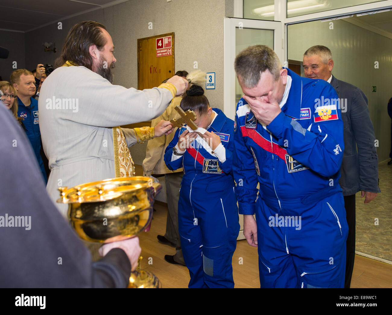 Expedition 41 Flight Engineer Elena Serova of the Russian Federal Space Agency (Roscosmos), left, receives the traditional - Stock Image