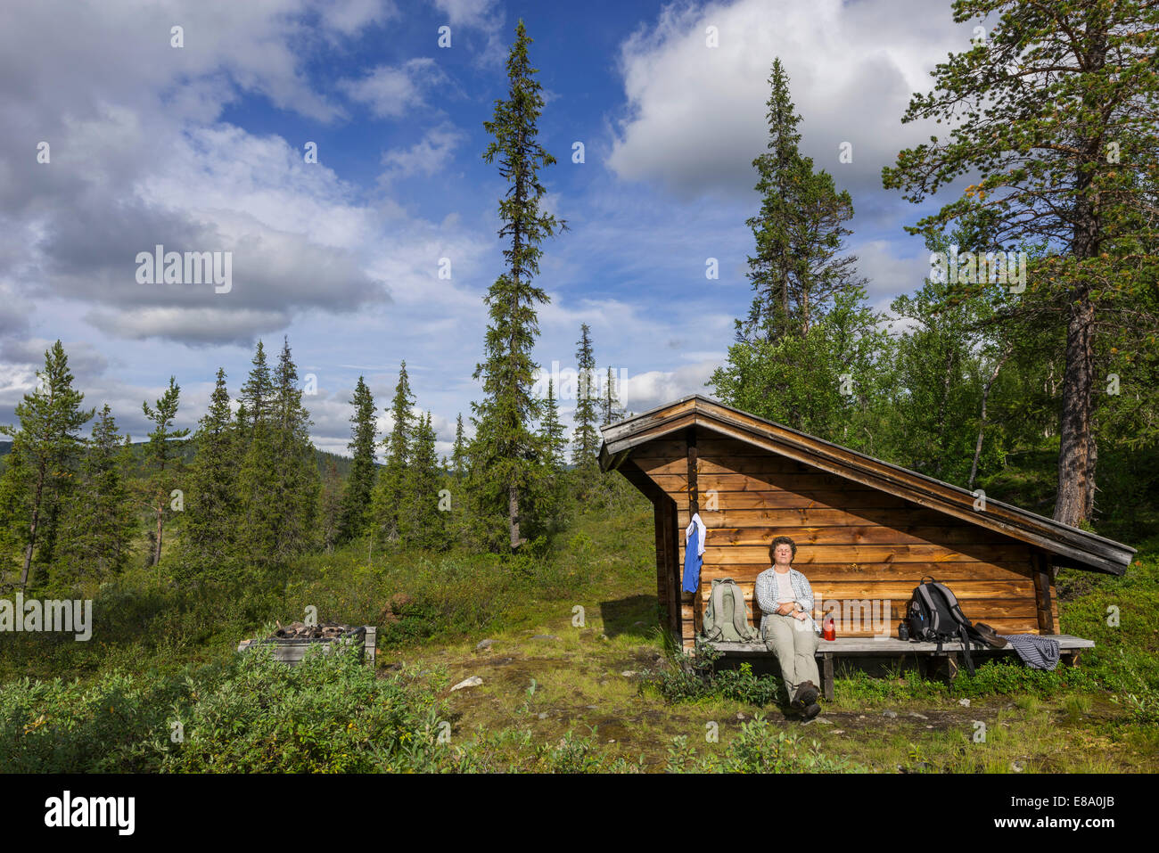 Woman resting at a wind shelter and campsite, Norrbotten County, Sweden - Stock Image