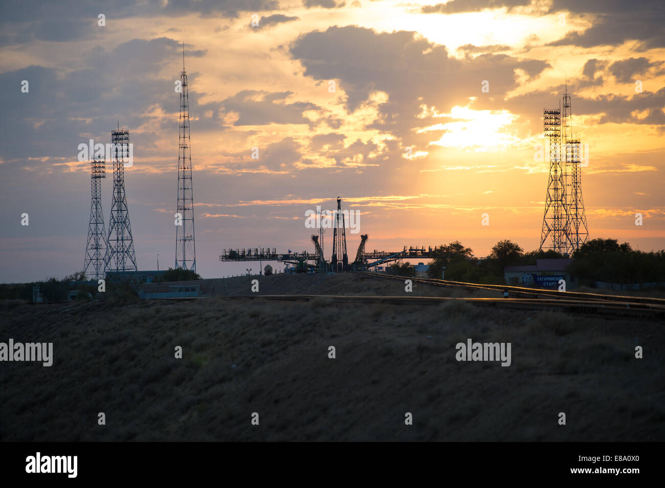 The sun rises behind the Soyuz launch pad as the Soyuz TMA-14M spacecraft is rolled out by train to the launch pad - Stock Image
