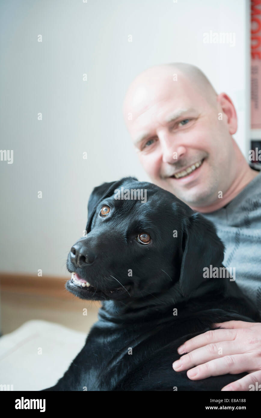 Portrait of man with his dog, smiling - Stock Image