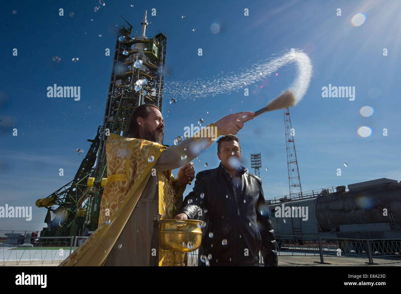 An Orthodox priest blesses members of the media at the Baikonur Cosmodrome launch pad on Wednesday, Sept. 24, 2014, - Stock Image