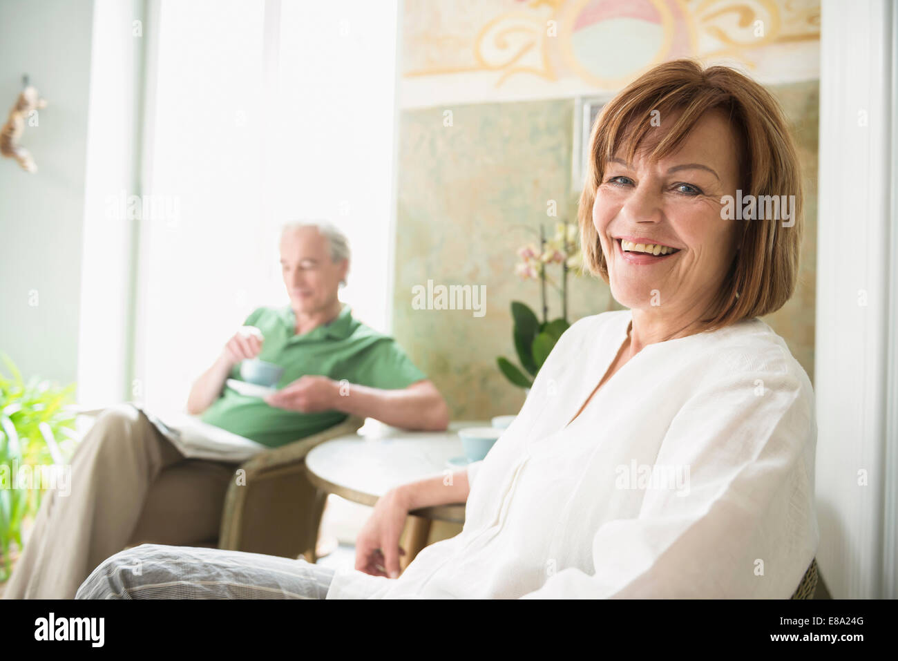 Portrait of senior woman smiling while mature man in background - Stock Image