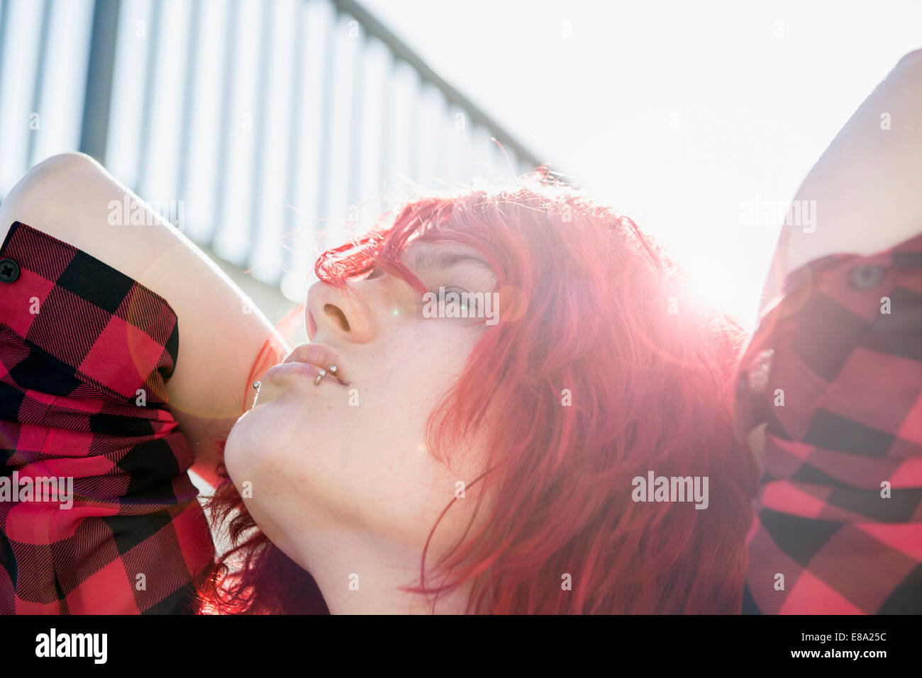 Teenage girl portrait day-dreaming red dyed hair - Stock Image