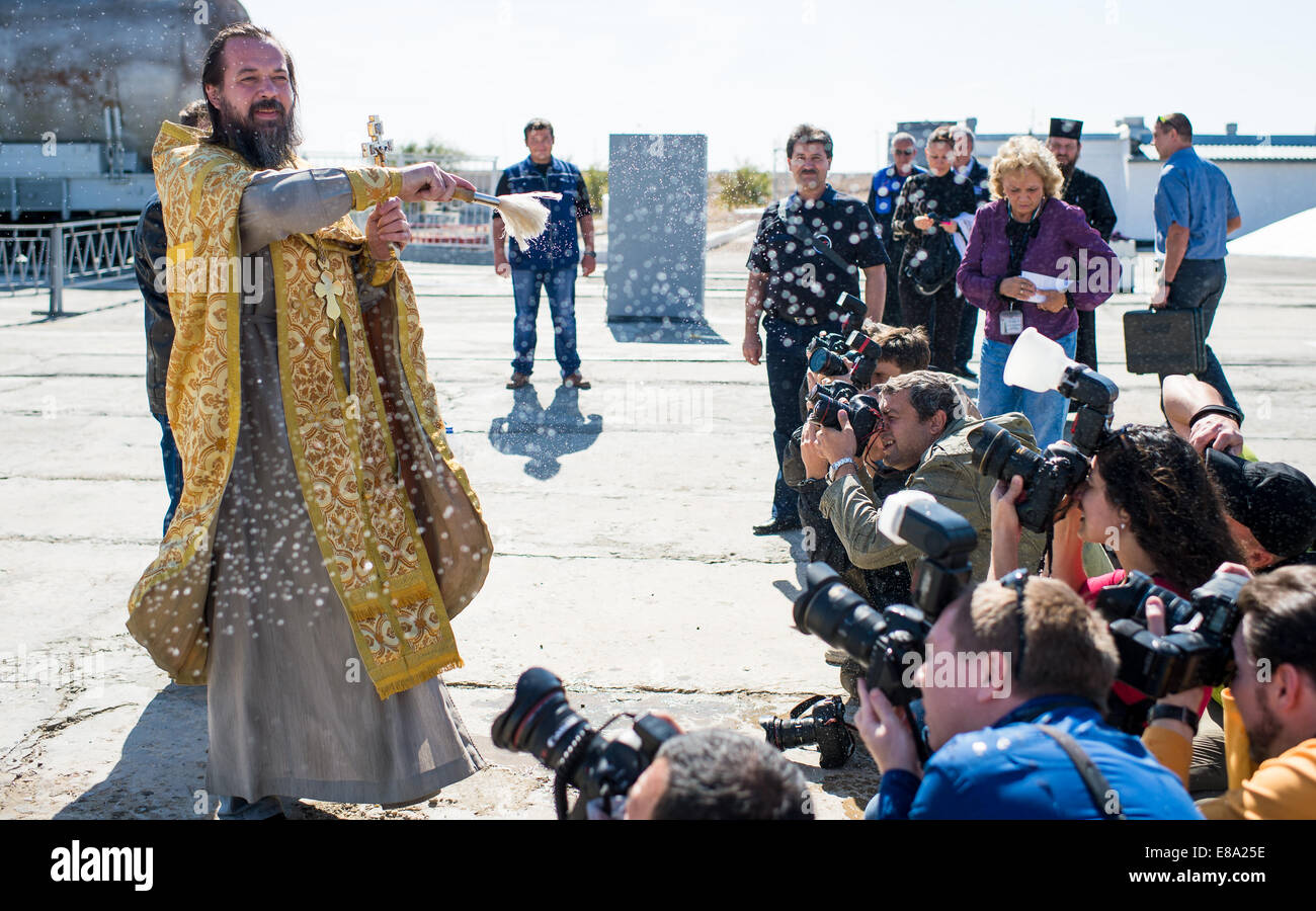 An Orthodox priest blesses members of the media at the Baikonur Cosmodrome launch pad on Wednesday, September 24, Stock Photo