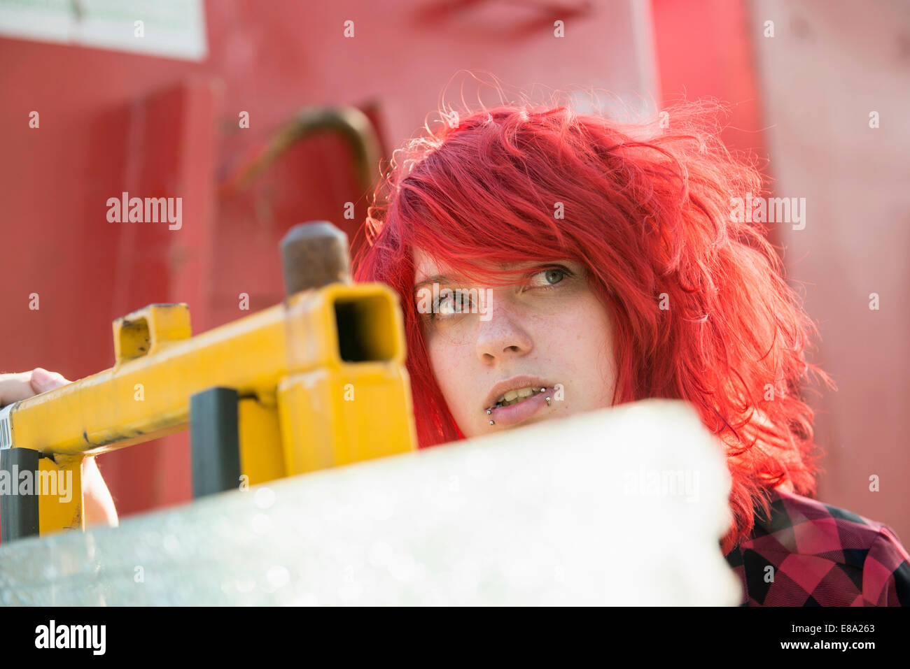 Young teenage girl dyed red hair piercings - Stock Image
