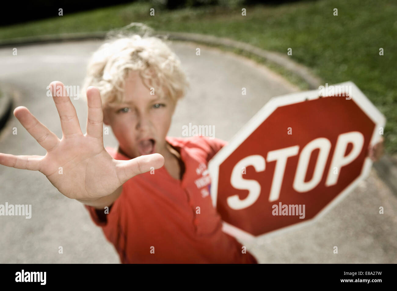 Boy on driver training area holding stop sign - Stock Image