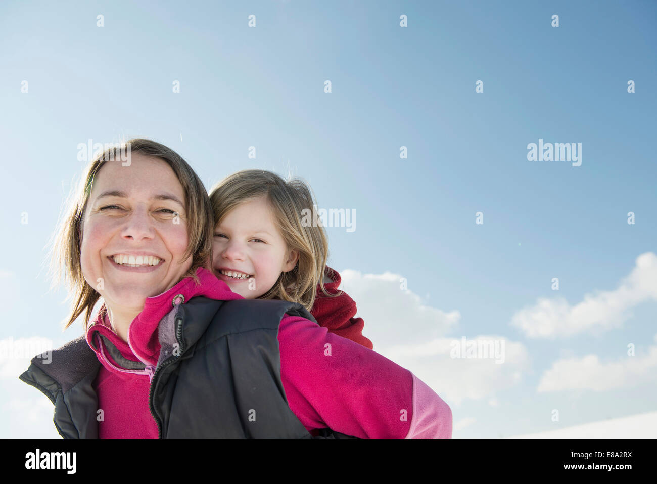 Mother giving piggyback ride to daughter, smiling, Bavaria, Germany - Stock Image