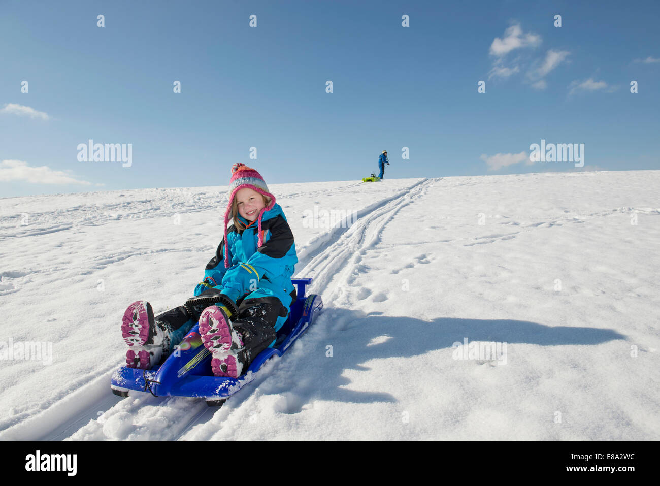 Girl sledging down hill, boy in background, Bavaria, Germany - Stock Image