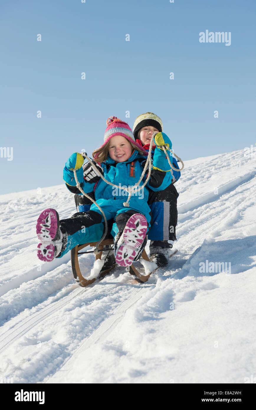 Brother and sister sledging down hill, smiling, Bavaria, Germany - Stock Image