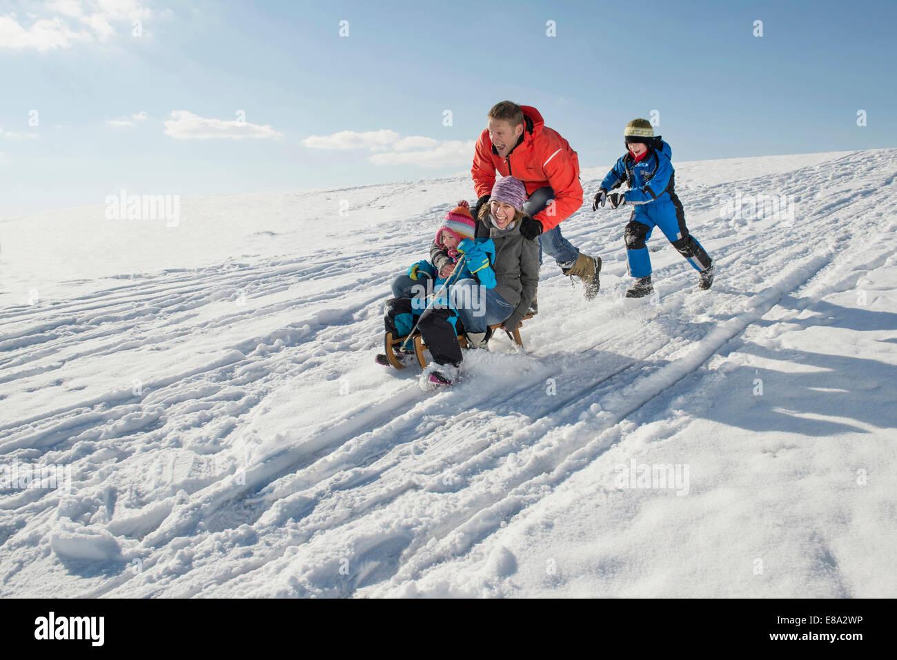 Family riding sledge, smiling, Bavaria, Germany - Stock Image