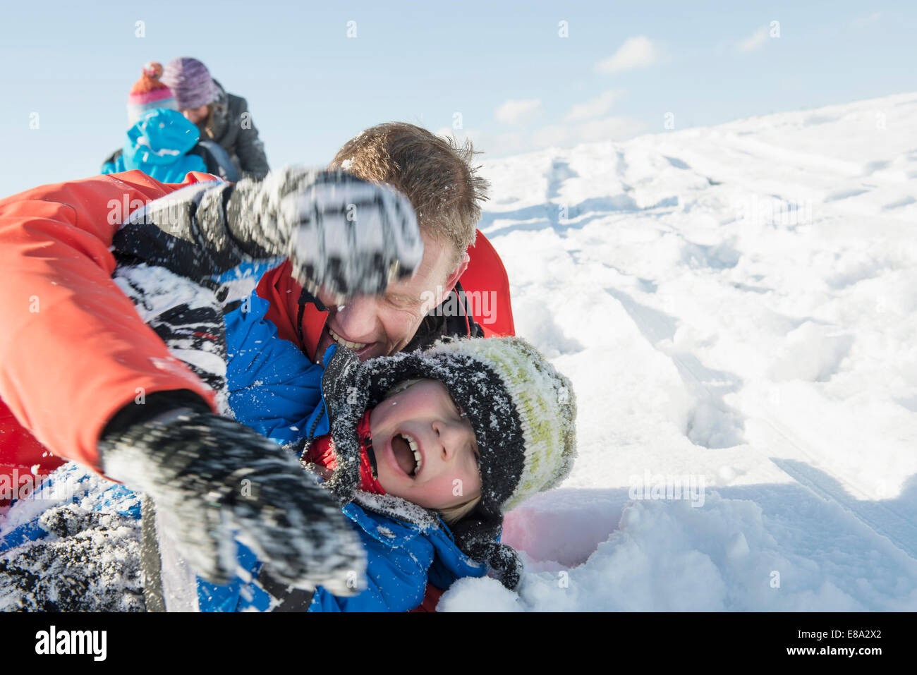 Family tussle in snow, smiling, Bavaria, Germany Stock Photo