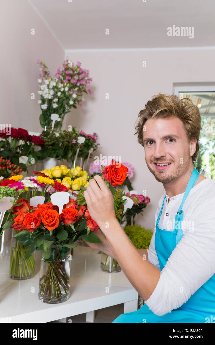 Portrait of mid adult man arranging flowers in vase, smiling - Stock Image