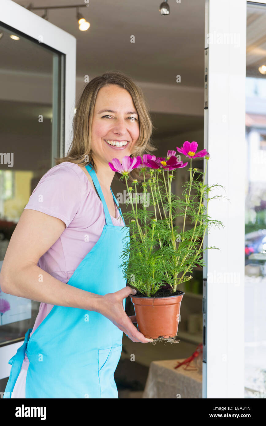 Portrait of mid adult woman holding potted plant of flower, smiling Stock Photo