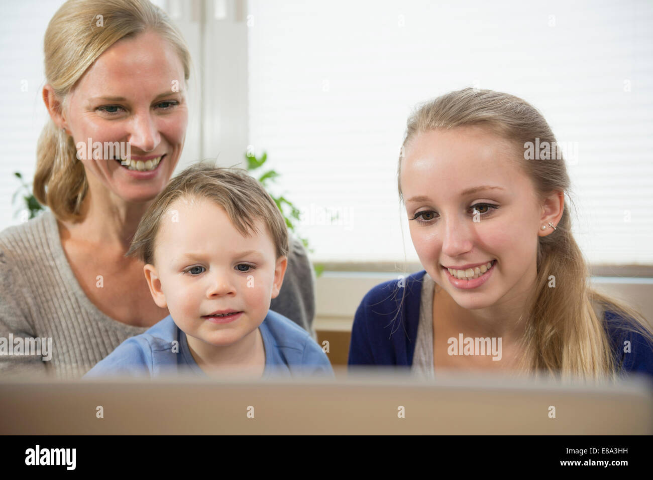 Mother, daughter and son being amused by something in internet - Stock Image