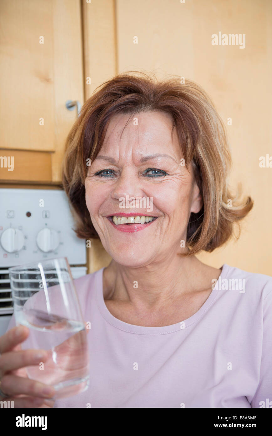 Portrait of senior woman in kitchen with water glass, smiling Stock Photo