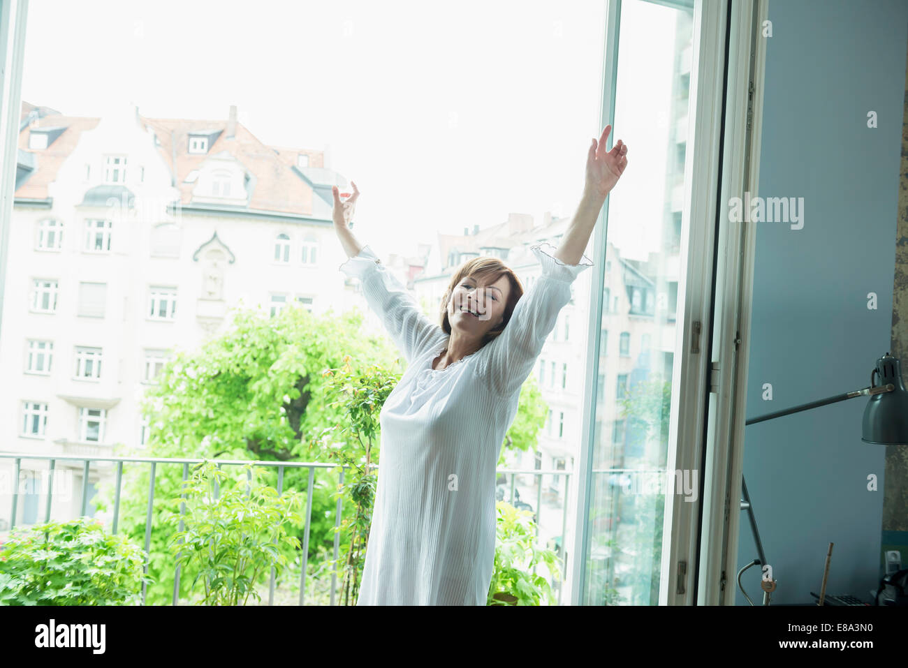 Senior woman stretching her body, smiling - Stock Image