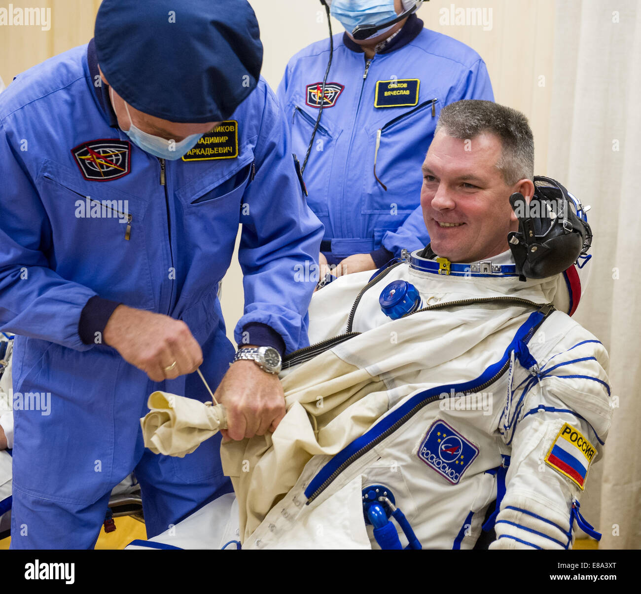 Expedition 41 Soyuz Commander Alexander Samokutyaev of the Russian Federal Space Agency (Roscosmos) is helped into - Stock Image