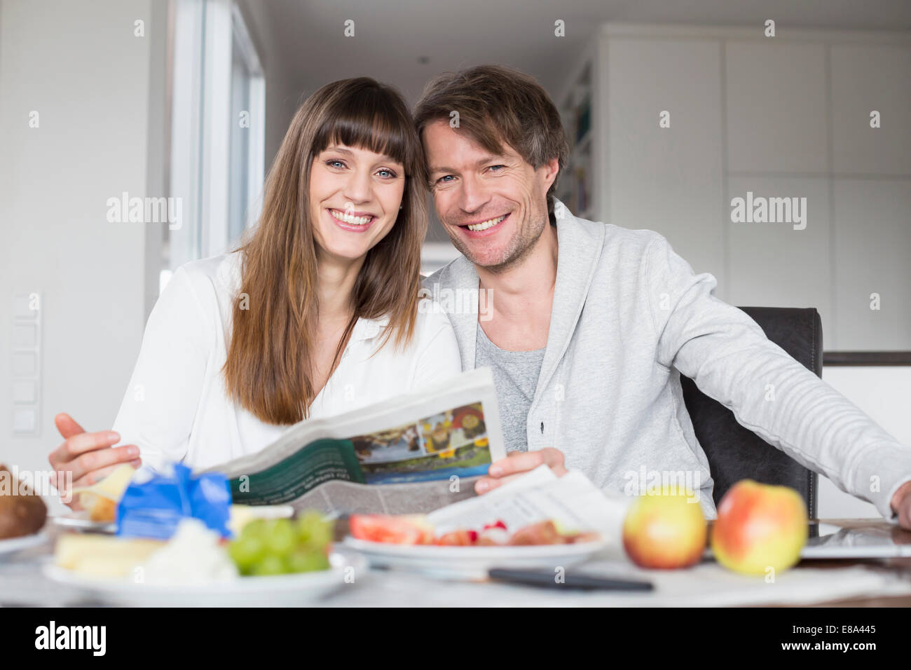 Portrait of couple having breakfast and reading newspaper together, smiling Stock Photo