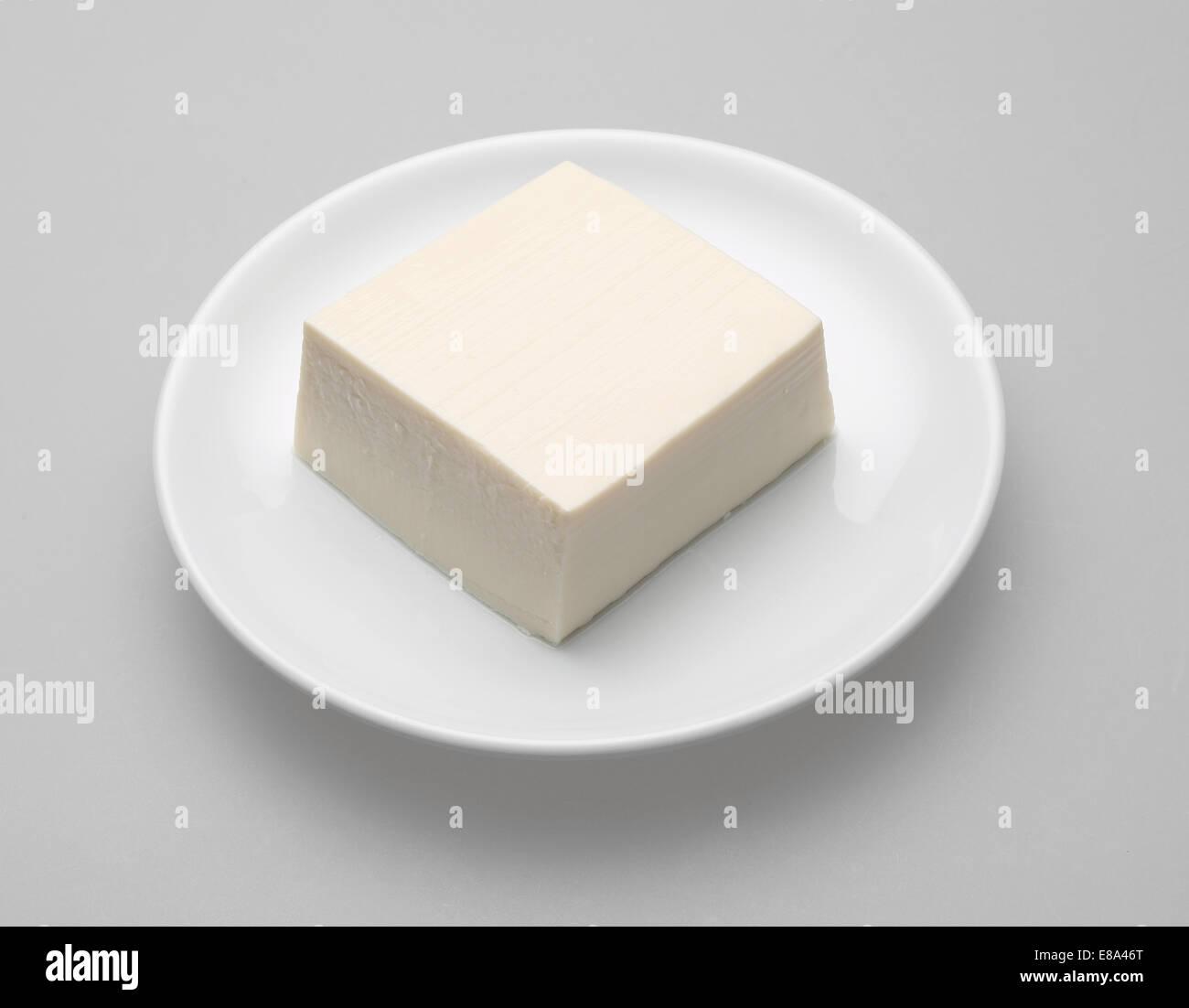Tofu on white dish - Stock Image