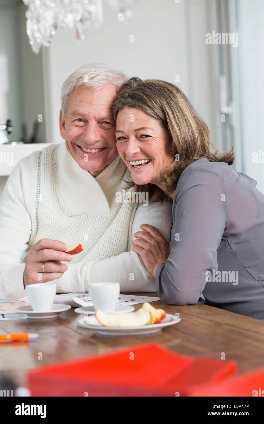 Happy couple at dining table eating appple - Stock Image