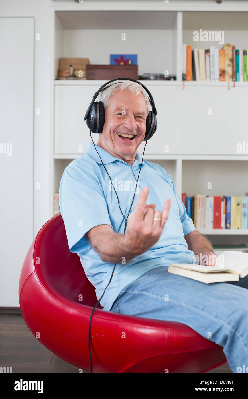 Senior man sitting in armchair listening to music - Stock Image