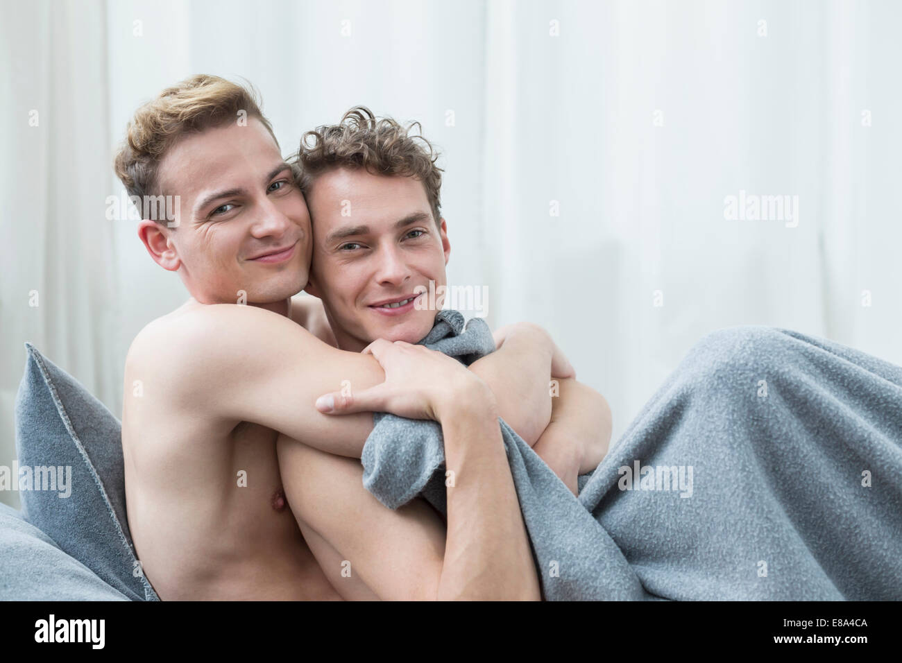 Portrait of homosexual couple embracing each other, smiling - Stock Image