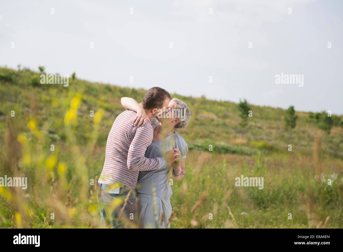 mature couple kissing in field stock photo: 73981789 - alamy