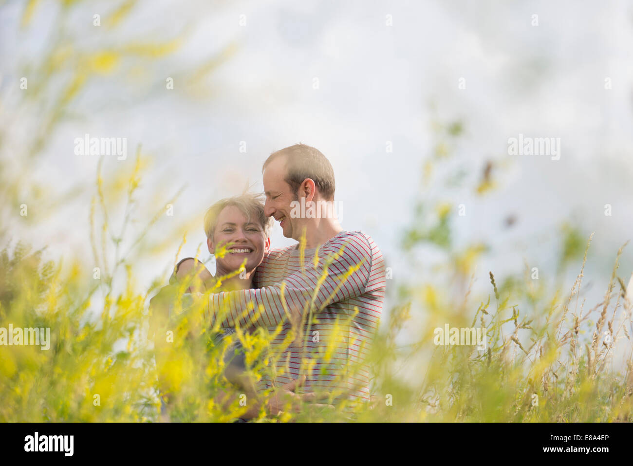 Mature couple embracing each other in field, smiling - Stock Image