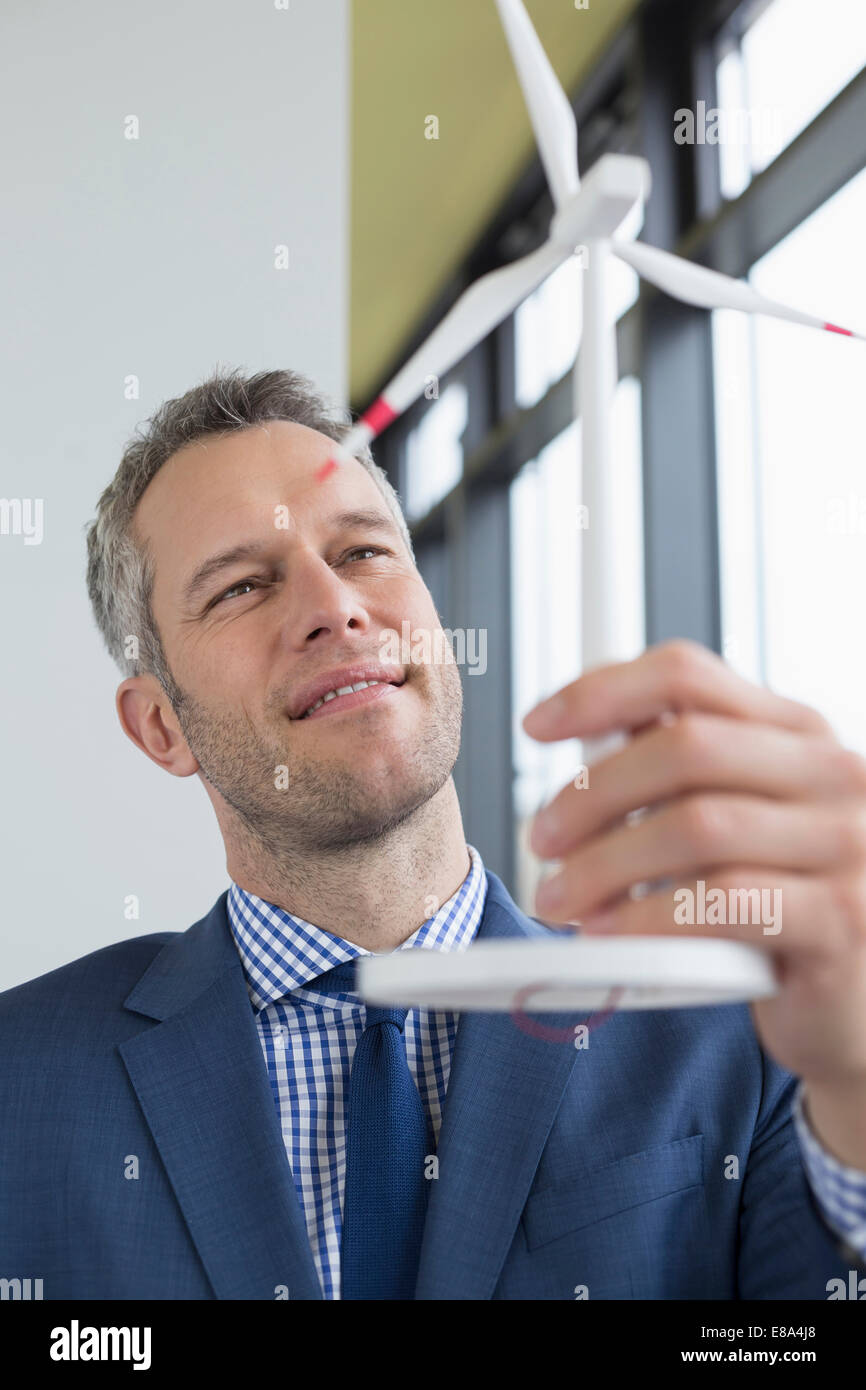 Businessman holding wind power model, smiling - Stock Image