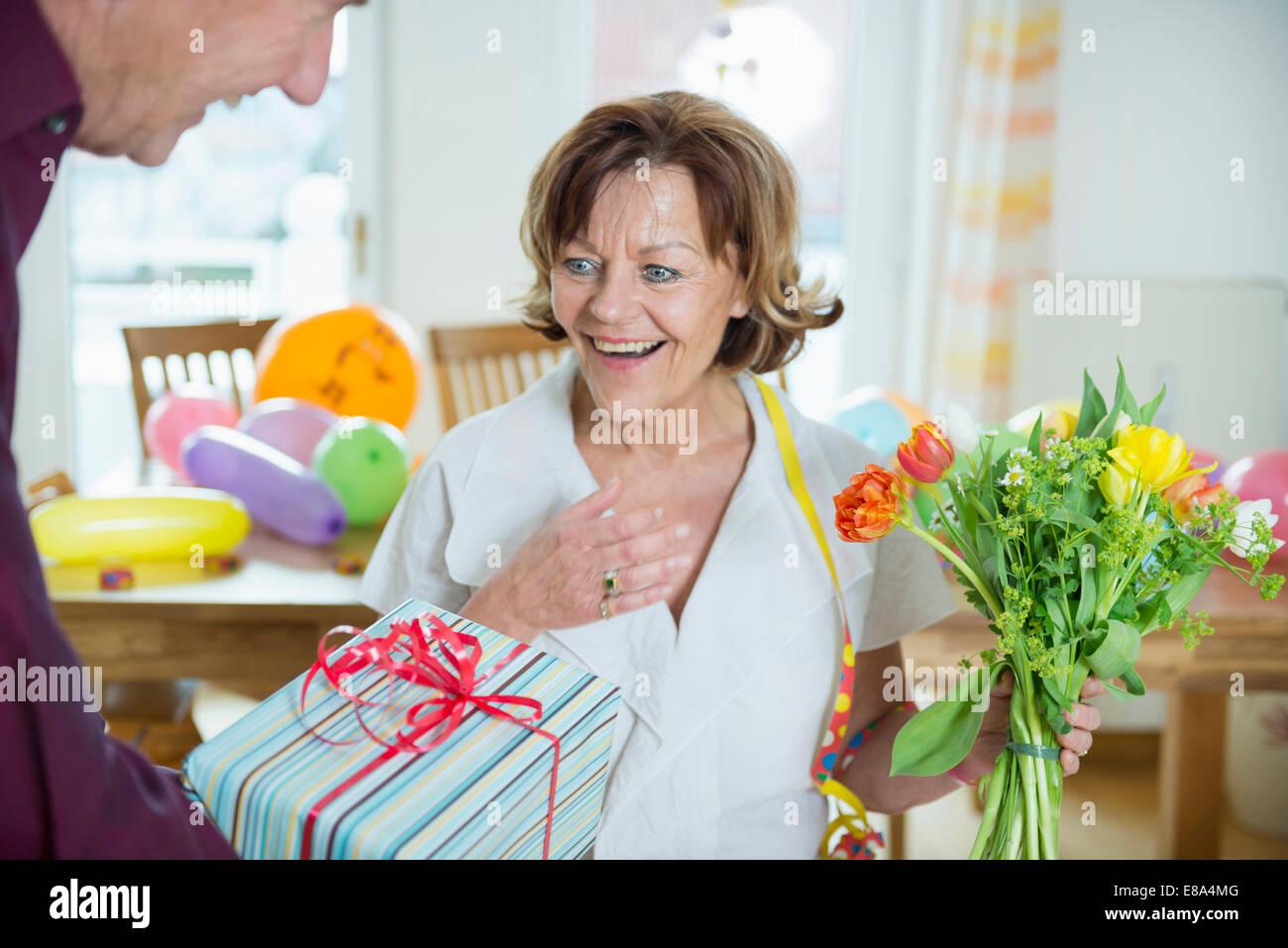 Senior man hand over present to woman on birthday, smiling - Stock Image