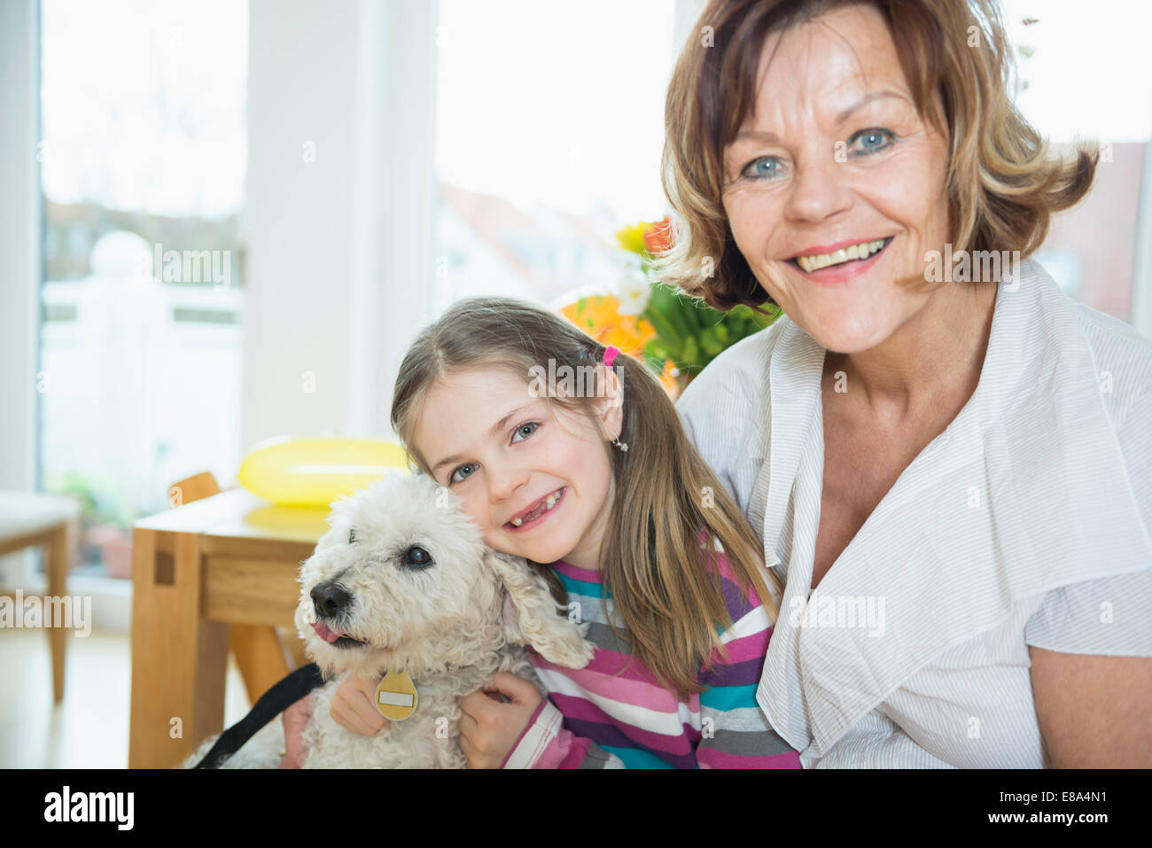 Portrait of grandmother and grandchild with dog in living room, smiling - Stock Image