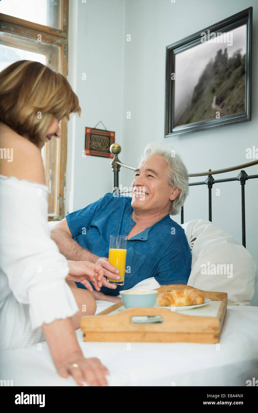 Couple having breakfast in bed, smiling - Stock Image