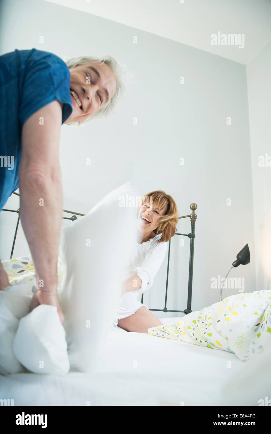 Couple having pillow fight in bed, smiling - Stock Image