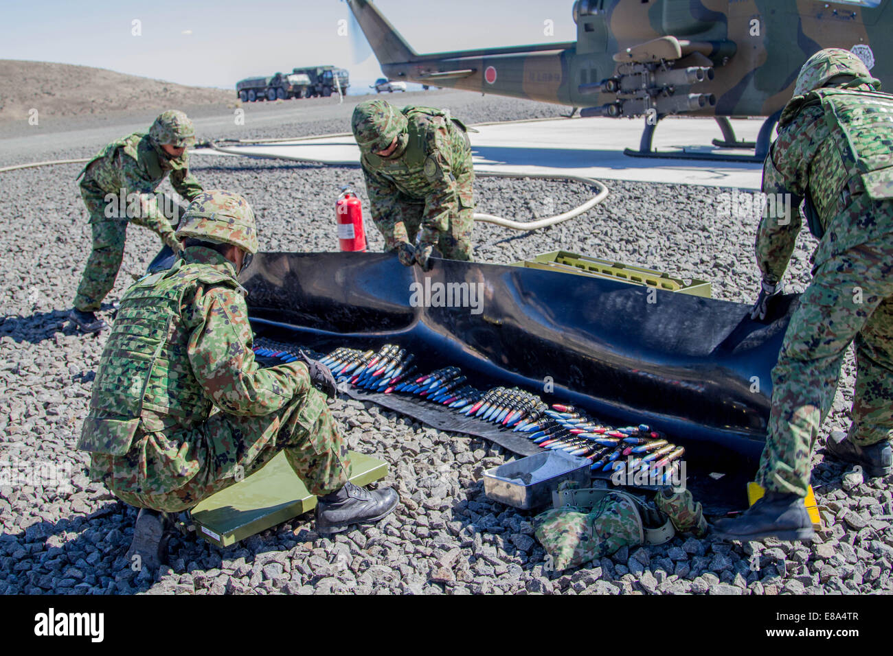 Japan Ground Self-Defense Force soldiers prepare ammunition to be loaded into the 20 mm cannon of an AH-1S Cobra Stock Photo