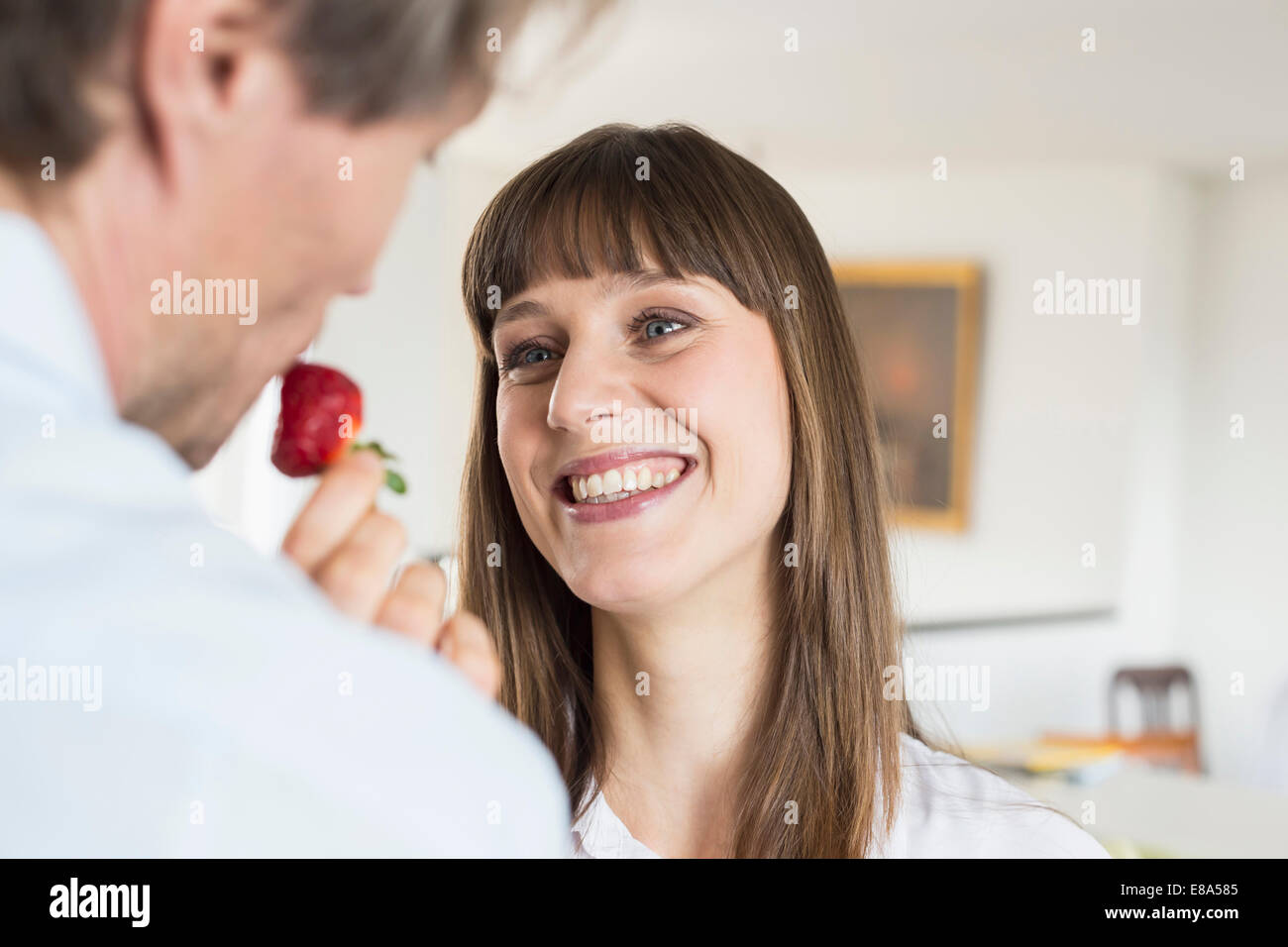 Mid adult woman feeding strawberry to mature man, smiling - Stock Image