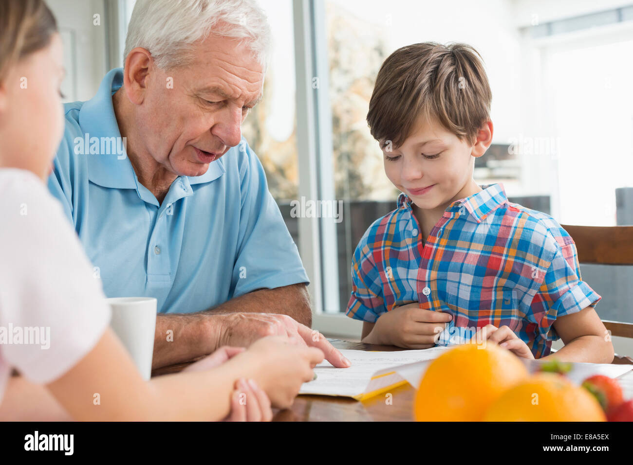 Children doing homework with their grandfather - Stock Image