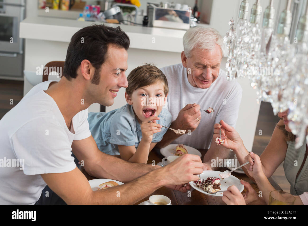 Extended family at table eating cake - Stock Image