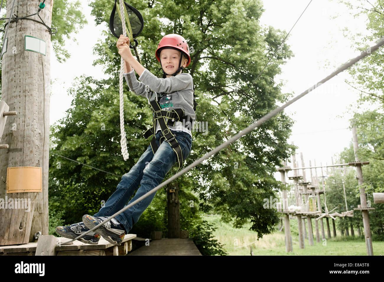 Boy climbing crag, smiling - Stock Image
