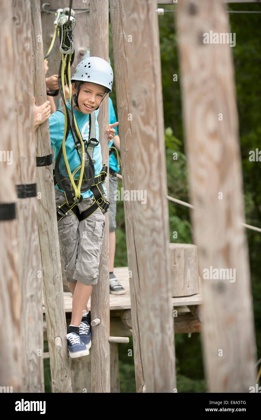 Boys climbing crag, smiling - Stock Image