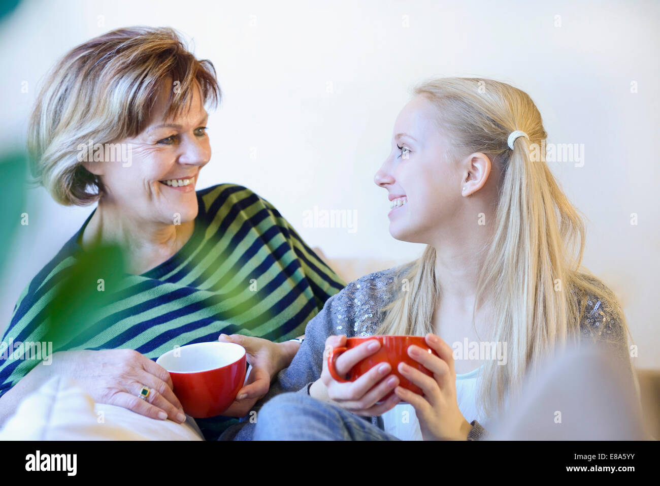 Grandmother and granddaughter in conversion on couch - Stock Image