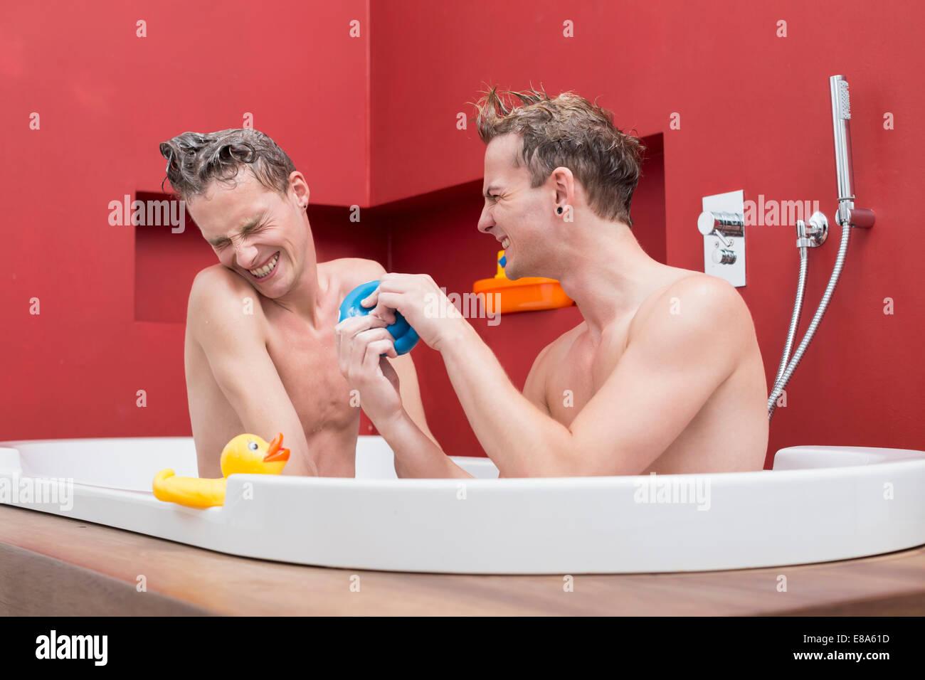 Homosexual Couple Having Fun In Bathtub Smiling Stock Photo