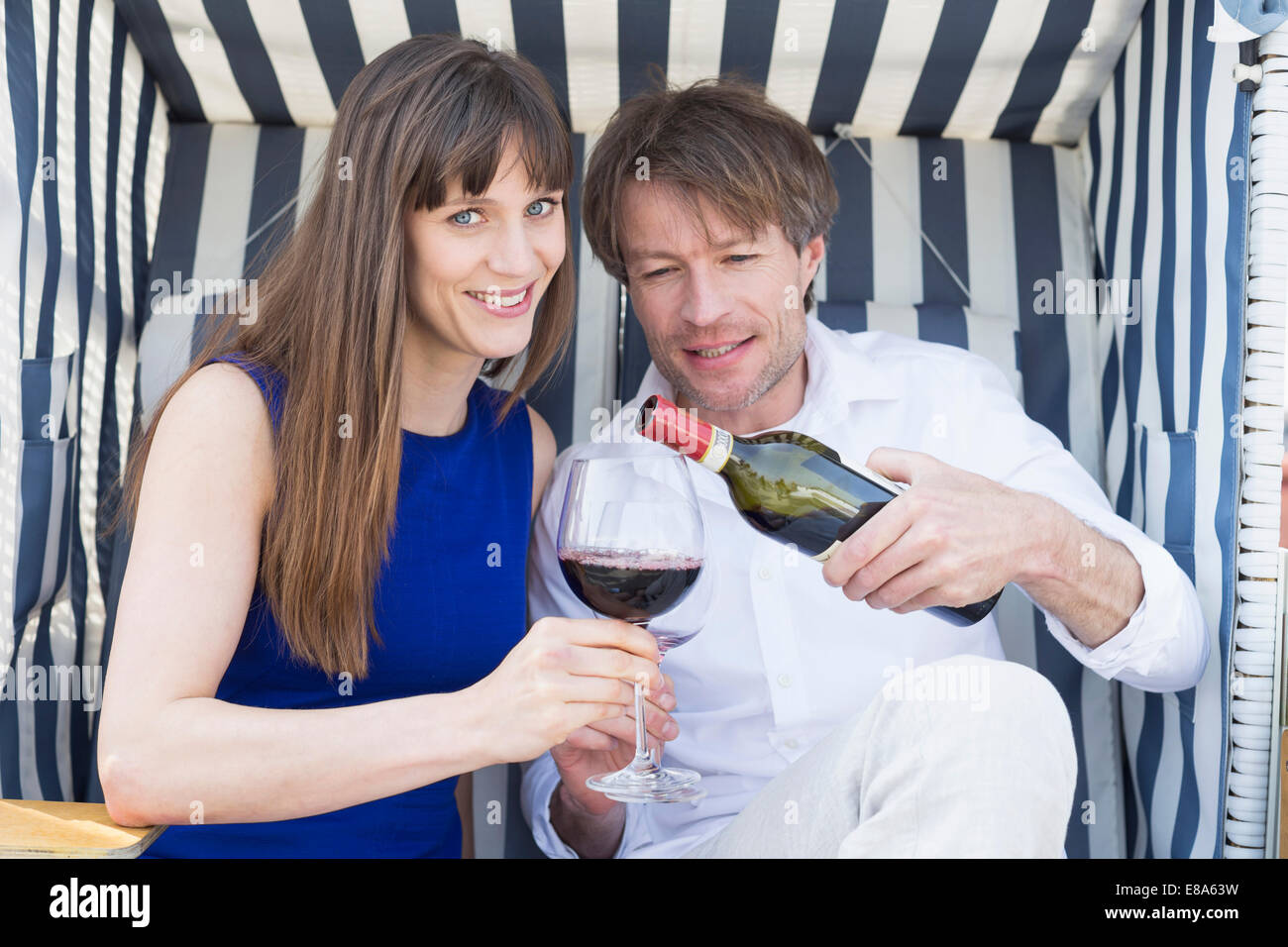 Couple having vine in roofed wicker beach chair, smiling Stock Photo
