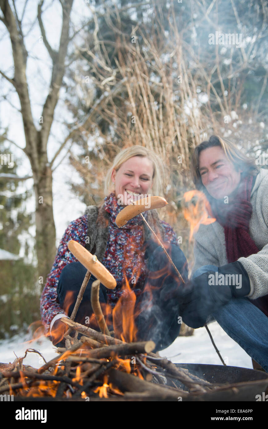 Couple barbecueing sausage on camp fire, Bavaria, Germany - Stock Image