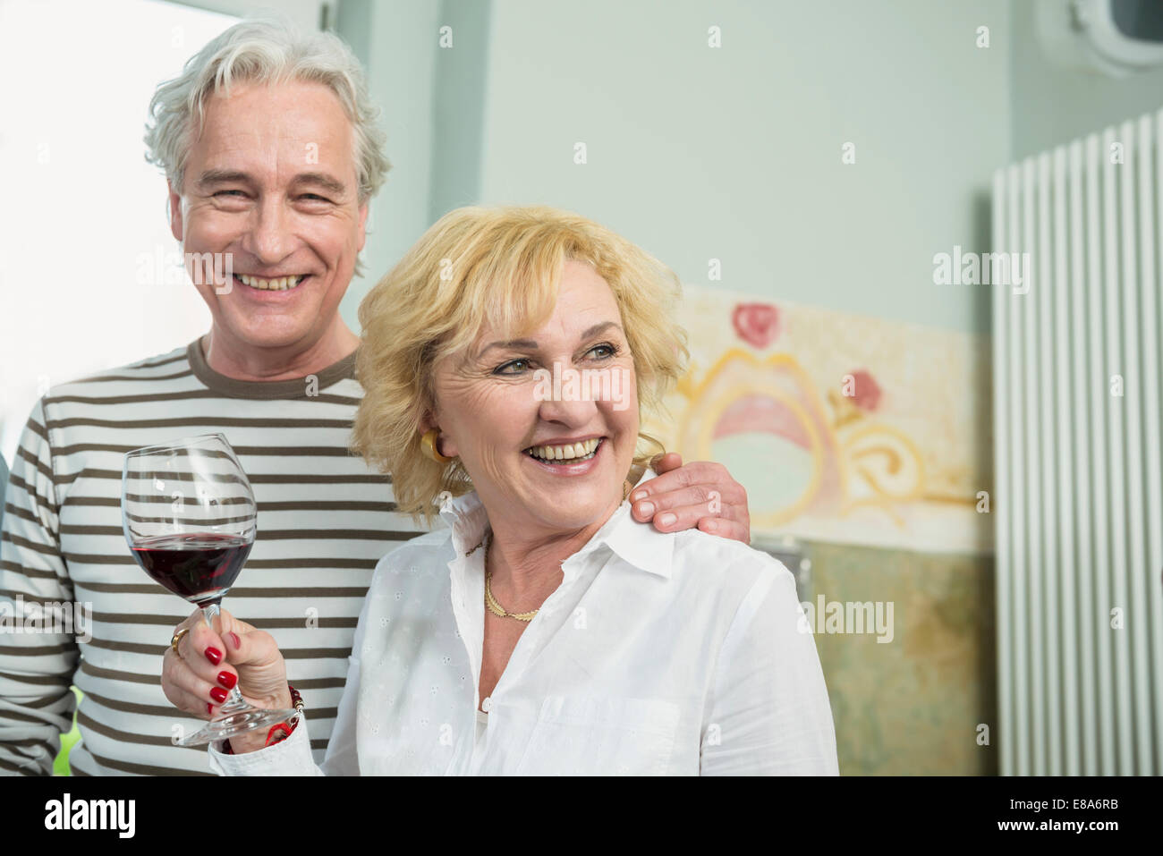 Mature couple drinking wine, smiling - Stock Image