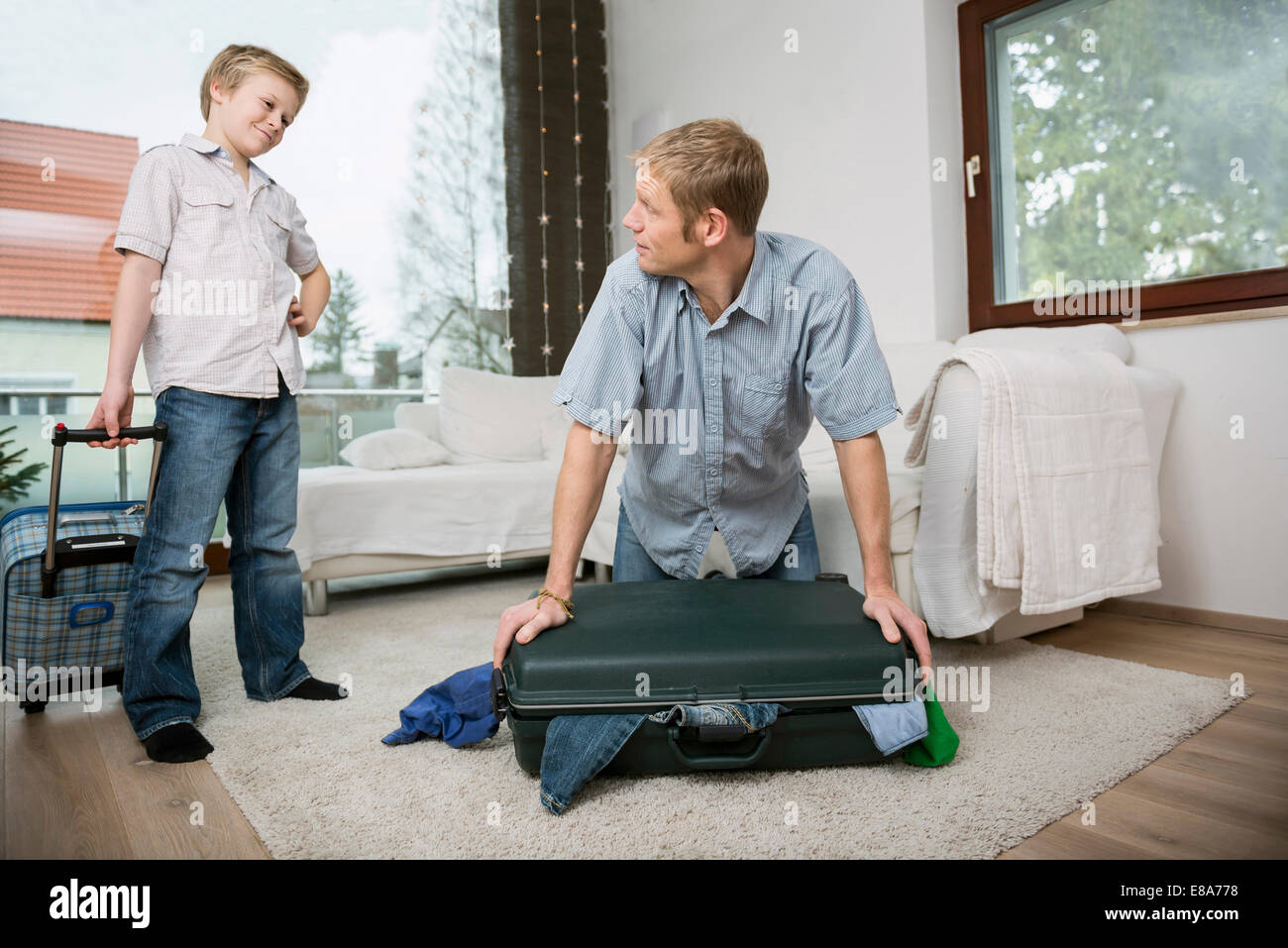 Father and son packing suitcase - Stock Image