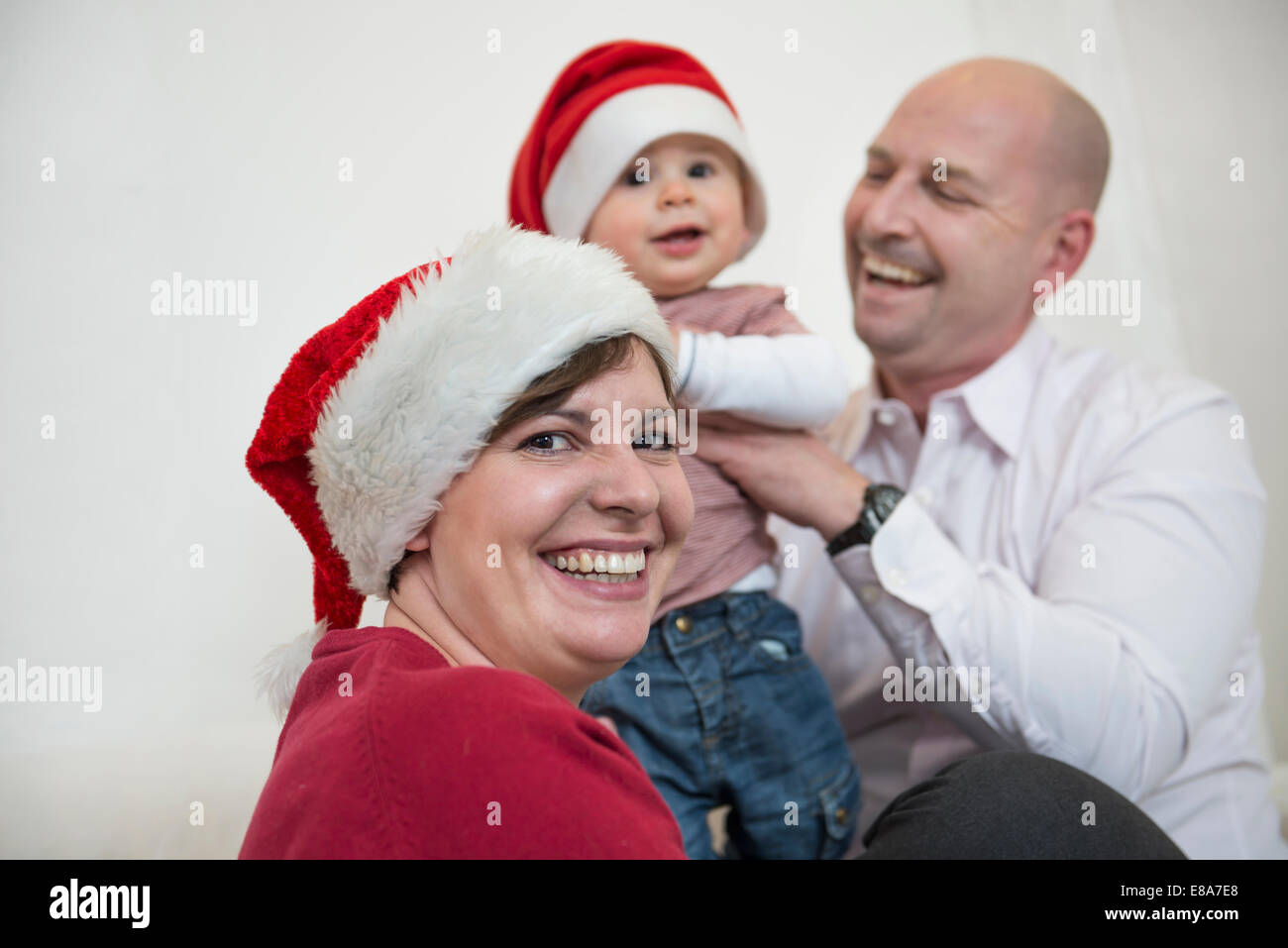 Family celebrating Christmas with Christmas caps - Stock Image