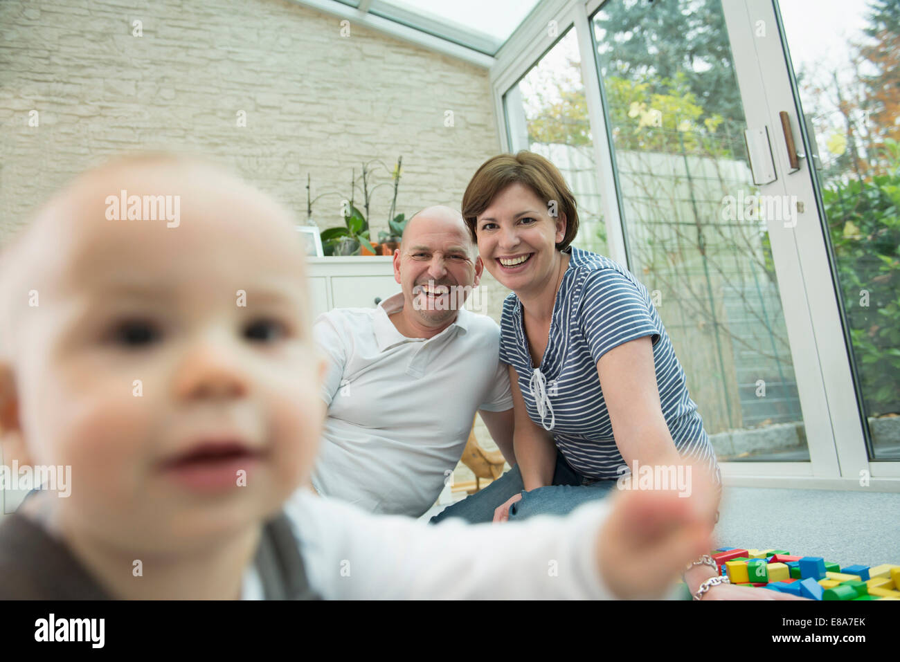 Parents and little son sitting on ground of living room Stock Photo